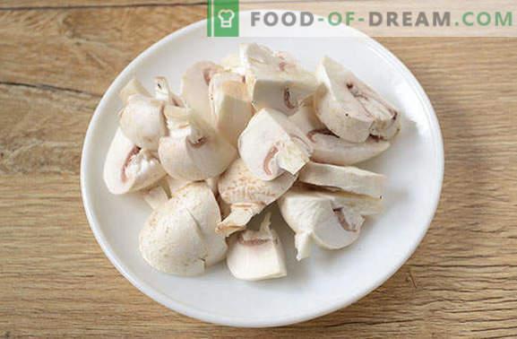 Rooster met varkensvlees en champignons in een pan - een man zal